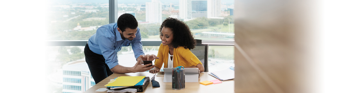 man showing woman his phone in office